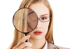 Businesswoman looking into a magnifying glass Royalty Free Stock Image