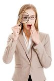 Businesswoman looking into a magnifying glass Stock Photos