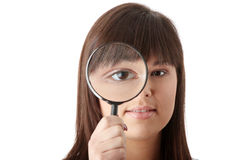 Businesswoman looking into a magniying glass Royalty Free Stock Photography