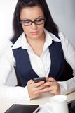 Businesswoman looking at mobile phone royalty free stock photography