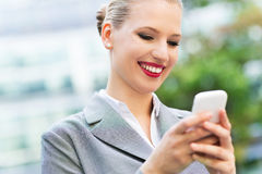 Businesswoman looking at mobile phone Stock Images
