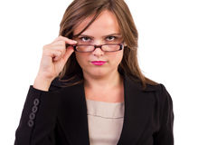 Businesswoman looking over  glasses. Against white background Stock Photo