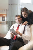 Businesswoman looking over male colleagues shoulder pointing at digital tablet Royalty Free Stock Images