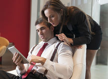 Businesswoman looking over male colleagues shoulder pointing at digital tablet Stock Photography