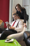 Businesswoman looking over male colleagues shoulder pointing at digital tablet Stock Images