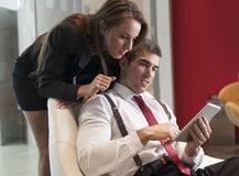 Businesswoman looking over male colleagues shoulder pointing at digital tablet Royalty Free Stock Photography