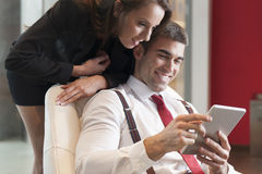 Businesswoman looking over male colleagues shoulder pointing at digital tablet Stock Photos