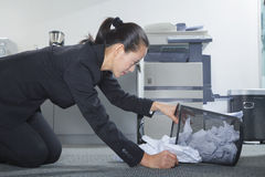Businesswoman Looking for Papers in Trashcan stock image