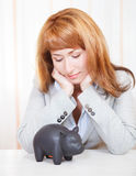 Businesswoman looking at the piggy bank. Sad businesswoman looking at the piggy bank Stock Image