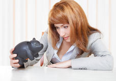 Businesswoman looking at the piggy bank. Sad businesswoman looking at the piggy bank Stock Photography