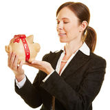 Businesswoman looking at piggy bank Royalty Free Stock Photos