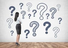 Businesswoman looking at question marks on wall Stock Images