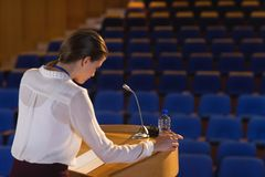 Businesswoman looking in script and trying to speak in the empty auditorium. Side view of blonde Caucasian businesswoman looking in script and trying to speak in stock photography