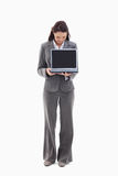 Businesswoman looking and showing a laptop screen. Against white background Stock Images