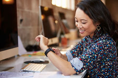 Businesswoman Looking At Smart Watch In Design Office Royalty Free Stock Photography