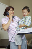 Businesswoman Looking At Son While On Call Stock Photography