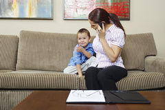 Businesswoman Looking At Son While On Call. Business women looking at son while communicating on cell phone at home stock image