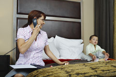Businesswoman Looking At Son While On Call In Bedroom Stock Images