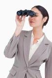 Businesswoman looking through spy glasses Royalty Free Stock Photos