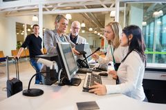 Businesswoman Looking At Staff Working At Airport Check-in. Senior businesswoman looking at female staff working at desk in airport Stock Image
