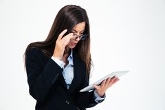 Businesswoman looking on tablet computer. Amazed businesswoman in glasses looking on tablet computer isolated on a white background Stock Photography