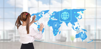 Businesswoman looking to global business map. Businesswoman standing in modern office and looking to global business map. Elements of this image furnished by stock image
