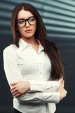 Businesswoman looking to the side. Businesswoman wearing glasses in front of a striped background looking to the side Stock Images