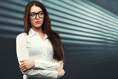 Businesswoman looking to the side. Businesswoman wearing glasses in front of a striped background looking to the side Royalty Free Stock Photos