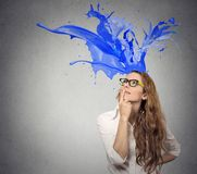 Businesswoman looking up with colorful splashes coming out of her head Stock Image