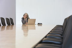 Businesswoman Looking Up By Laptop In Board Room Royalty Free Stock Photos
