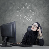 Businesswoman looking up with lightbulb. Young businesswoman wearing glasses having an idea and looking up with lightbulb over her head while sitting in front of Stock Image