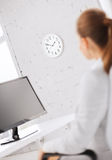 Businesswoman looking at wall clock in office Royalty Free Stock Photography