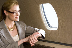 Businesswoman looking at watch on aeroplane, close-up stock photos