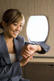 Businesswoman looking at watch on aeroplane, smiling, close-up Stock Image
