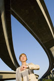 Businesswoman looking at watch beneath overpasses, low angle view Royalty Free Stock Photography
