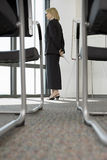 Businesswoman looking through window in conference room, empty chairs in foreground, surface level Royalty Free Stock Images