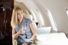 Businesswoman Looking Through Window Of Private. Beautiful businesswoman holding wineglass while looking through window of private jet Royalty Free Stock Photo