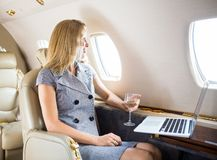 Businesswoman Looking Through Window Of Private. Happy businesswoman holding wineglass while looking through window of private jet royalty free stock photography