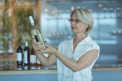 Businesswoman looking at winebottle Stock Photo