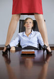 Businesswoman looking at woman standing on top of table in office Royalty Free Stock Photography