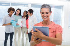 Businesswoman looks at tablet pc while coworkers stand behind her Stock Photos