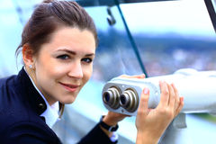 Businesswoman looks through telescope on the city Stock Images