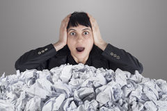 Businesswoman with lot of crumpled paper Stock Image