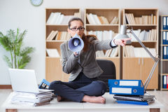 The businesswoman with loudspeaker in office. Businesswoman with loudspeaker in office Royalty Free Stock Photos
