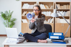 The businesswoman with loudspeaker in office. Businesswoman with loudspeaker in office Stock Photo