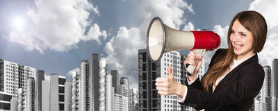 Businesswoman with loudspeaker. On the urban background Royalty Free Stock Photography
