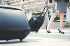 Businesswoman lower part walking and pulling luggage Royalty Free Stock Images