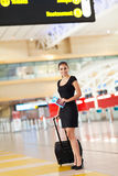 Businesswoman luggage airport. Beautiful young businesswoman with luggage standing at airport Stock Images