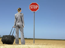 Businesswoman With Luggage Looking At Stop Sign Royalty Free Stock Photos