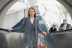 Businesswoman, with luggage, standing on escalator, smiling, front view, portrait, elevated view Stock Images
